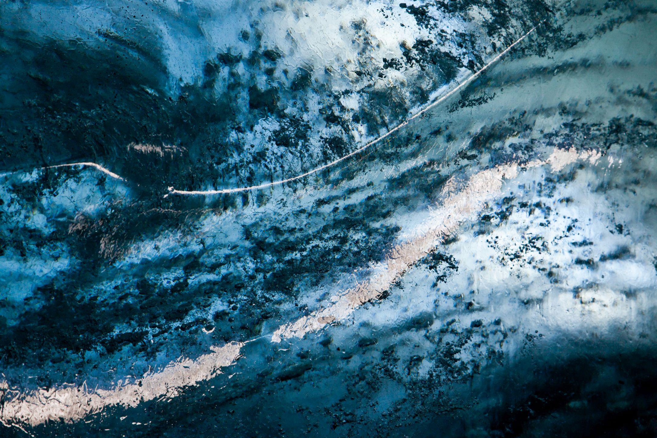 Morteratsch-Gletscher - Nördliche, untere Höhle - Auf- und Durchlicht an Eis-Höhlenwand: Auf der nördlichen Seite des Morteratsch-Gletscher in der neuen unteren Eis-Höhle. Mit Standort in der Höhle, etwas unterhalb der Mitte an der linken Eis-Wand. Diese Wand ist von einer kleinen Nebenhöhle, welche einen Eingang hat durchleuchtet. Ferner reflektiert vom unteren Eingang her Licht auf der Oberfläche. Der Ausschnitt beträgt cirka 20cm in der Länge. Das Eis an dieser Wand hat eine wellenförmige Oberfläche, daher ist nicht alles gleich weit entfernt. Scharf gestllt ist auf die feine weisse Linie.